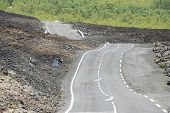 stock photo of french curves  - Curved asphalt road over volcanic lava - JPG