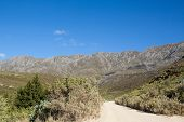pic of dirt road  - Dirt road leading over a high mountain pass in daytime - JPG
