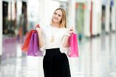 picture of boutique  - Cheerful attractive young woman enjoying shopping holding bright colored paper bags beside boutiques in outlet copyspace - JPG