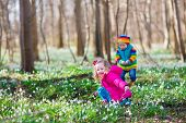 image of brother sister  - two little children cute toddler girl and funny baby boy brother and sister playing in a sunny forest with beautiful spring snowdrop flowers - JPG