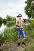 pic of sun perch  - Young man is fishing on the bank of the river - JPG