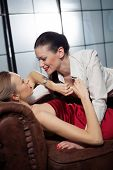 stock photo of sado-masochism  - Beautiful lesbian flirting couple on the sofa - JPG