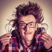 pic of nerd  - Smiling young nerd holding light bulbs - JPG