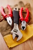 foto of wire cutter  - Adjustable wrench pliers and wire cutters on top of the protective gloves on a wooden background - JPG