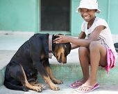 stock photo of tween  - A tween Haitian girl happily petting a large black dog - JPG