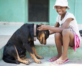 picture of tween  - A tween Haitian girl happily petting a large black dog - JPG