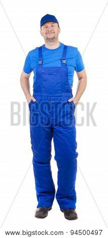 Man in blue overalls with hands in pockets.
