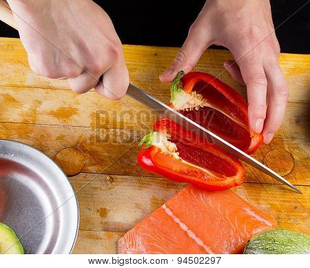 Chef Slicing Tomato On A Wooden Board