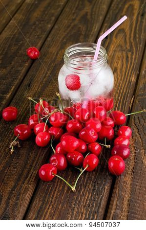 Cold Drink In A Jar With Pink Straw Among Several Cherries