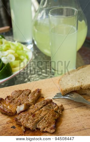 Pork Steak In Front Of Glass And Jar With Cucumber Lemonade