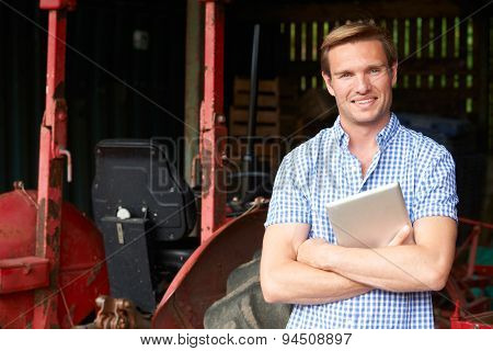 Portrait Of Farmer With Old Fashioned Tractor And Digital Tablet
