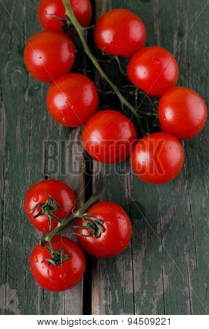 Several Red Cherry Tomatoes On Branch Placed On Green Table