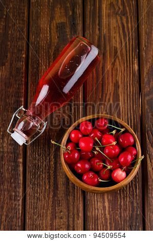 Top View On Full Glass Bottle And Full Bowl Of Cherries