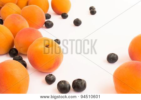 Apricots and Blueberries Scattered Against a White Background