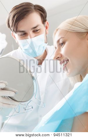 Smiling woman looking in mirror by dentist