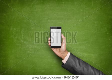 Businessman hand holding smartphone front of blackboard