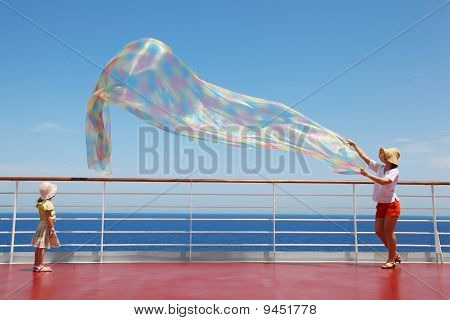 Mom And Her Daughter Play With Enormous Chiffon Scarf On Deck