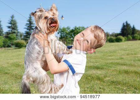 Pleasant little boy holding dog