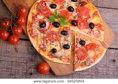 Piece Of A Pizza And Pizza From A Salami, A Ham And Tomatoes On A Wooden Table