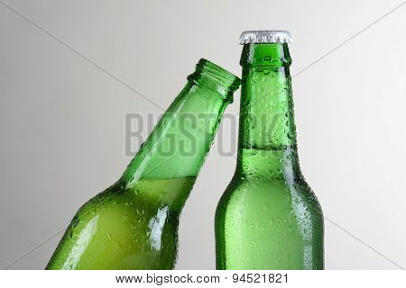 Closeup of two green beer bottles against a light to dark gray background. One bottle is at a slant leaning on the other bottle. Horizontal format with copy space.