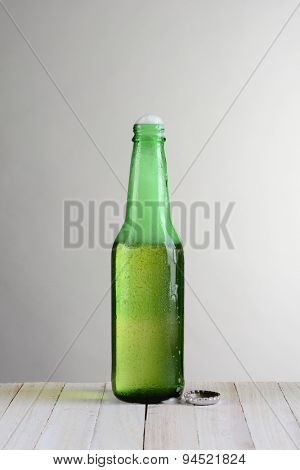 One green beer bottle on a wood table against a light to dark gray background. The bottle is open with foam coming out the open top. Vertical format with copy space.
