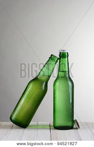 Two green beer bottles on a wood table against a light to dark gray background. One bottle is at a slant leaning on the other bottle. Vertical format with copy space.
