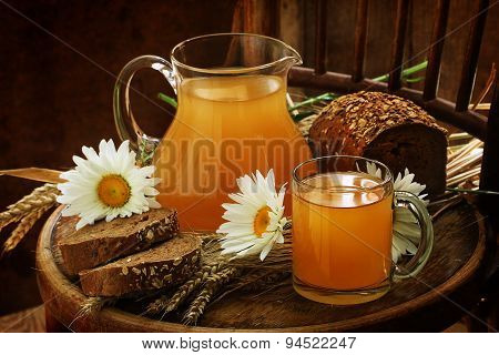 Kvass (kvas) In A Transparent Jug, Rye Bread And Camomiles On A Wooden Table