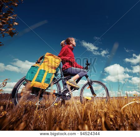 Hiker standing with loaded bicycle in the field