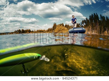 Split shot of the fisherman with rod in the boat and underwater view of the bright wobbler bait with hook