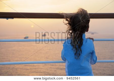 little girl wearing tracksuits is standing on deck of ship