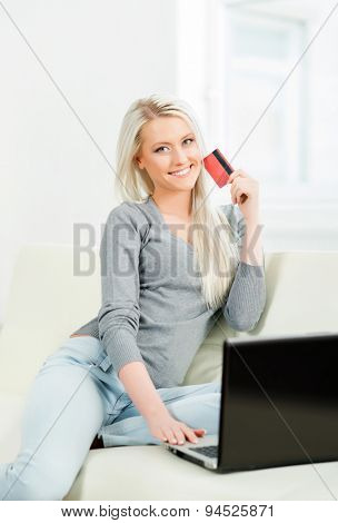 Online shopping concept. Beautiful blond girl with a credit card.