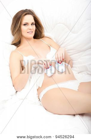 Pretty pregnant woman in a bed