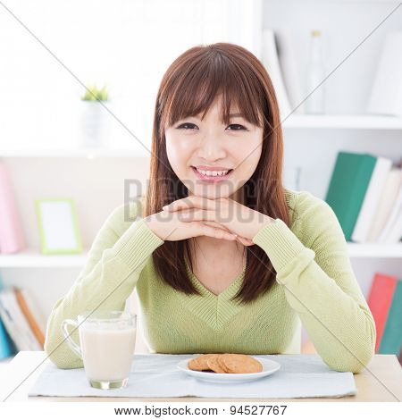 Portrait of happy Asian girl eating breakfast. Young woman indoors living lifestyle at home.