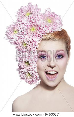 Emotional portrait of young pretty girl with violet contact lenses, fancy make-up, piercing and pink flowers in her hair over white background