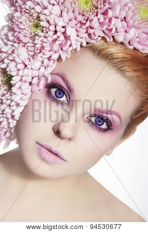 Portrait of young beautiful woman with violet contact lenses, fancy make-up and flowers in her hair