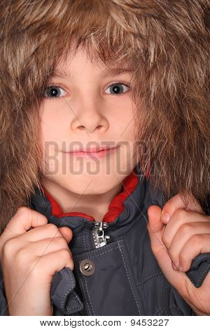 Portrait Of Little Boy In Big Fur Hood, Looking At Camera And Smiling