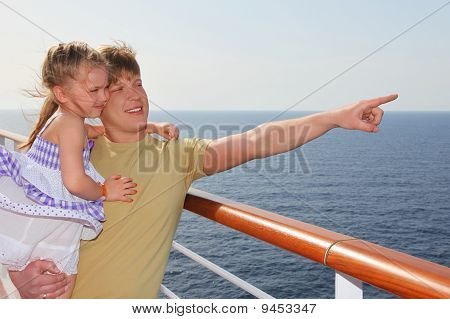 Father Standing On Cruise Liner Deck, Carrying His Daughter And Pointing For Finger At Right Side
