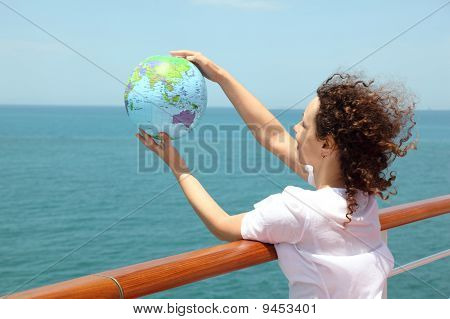 Young Curl Woman Standing On Cruise Liner Deck And Holding Globe