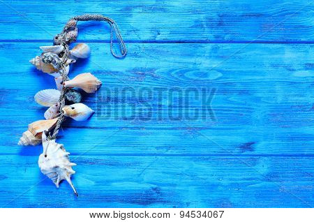 an ornament made from seashells and conchs on a blue rustic wooden surface, with a blank space