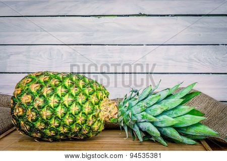 Pineapple On A Wooden Table With Linen