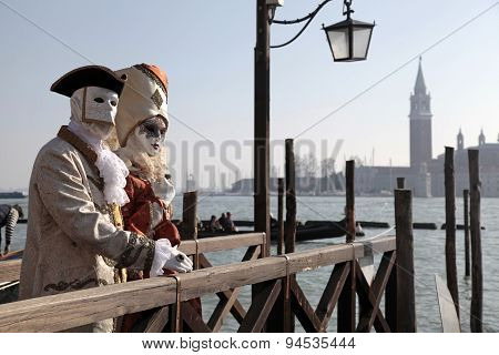 Person Wearing Venetian Mask And Posing Along Saint Mark Waterfront In Venice, Italy.