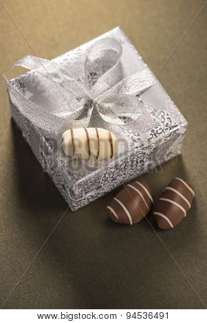 Silver gift box with few date chocolates.