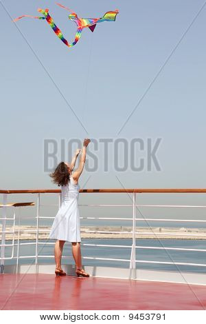 Young Brunette Woman Playing With Multicolored Kite, Standing On Cruise Liner Deck