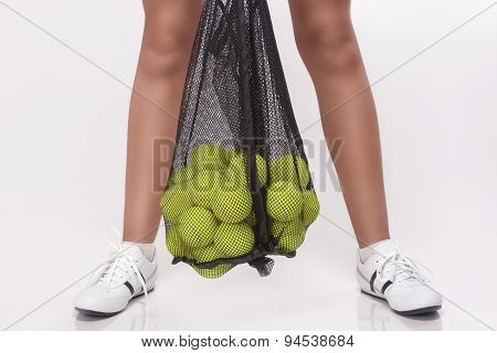 Closeup Of Female Legs Holding Tennis Balls In Mesh In Studio Environment