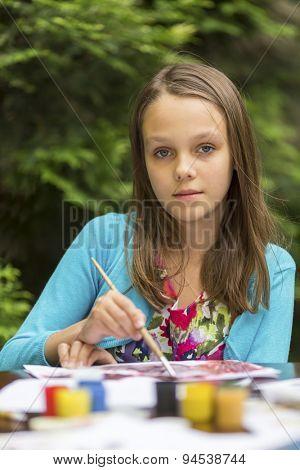 Close-up portrait of little cute girl draws paints.