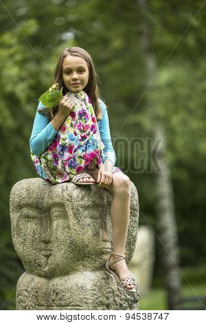 Cute little girl sitting on a stone totem in the Park.
