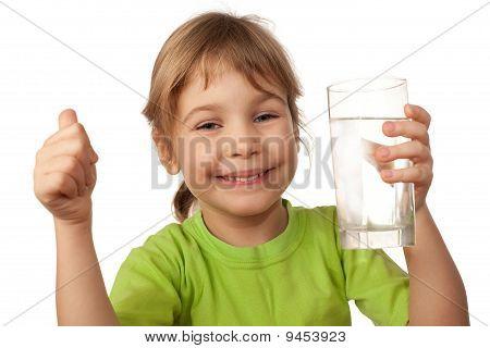 Niño pequeño beber agua del recipiente de vidrio