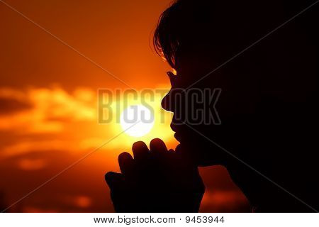 Silhouette of person in profile against background of orange sunset sky.