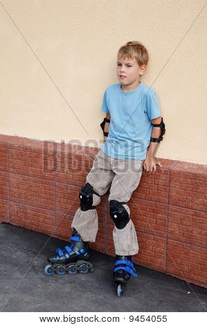 Boy in rollerblades knee and elbow pads standing near wall.