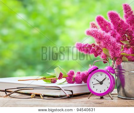 Vintage Still Life: Flowers In Bucket, Pink Alarm Clock And Bucket On Wooden Table Outdoors